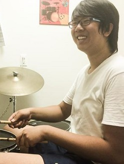 Yang is learning a new beat at his drum lessons.