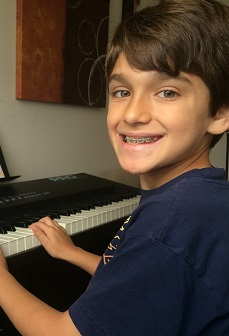 Student Eli enjoys his piano lessons.