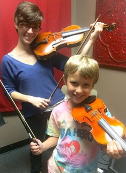 Charlie and his teacher have some fun in his violin lesson
